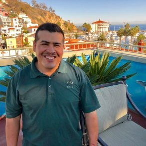 Staff of hotel - latino with black hair and dark teal shirt with Avalon logo on it