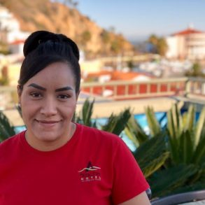 Staff of hotel - latina with black hair and red shirt with Avalon logo on it